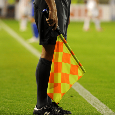 A curacao football referee member, standing on the football field with his flag.