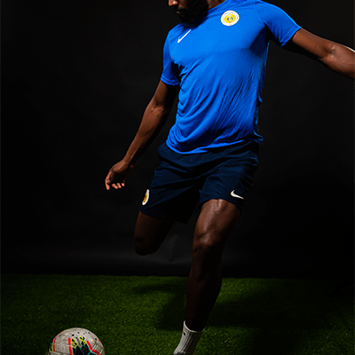 Cuco Martina, kicking a football with the FFK shirt.