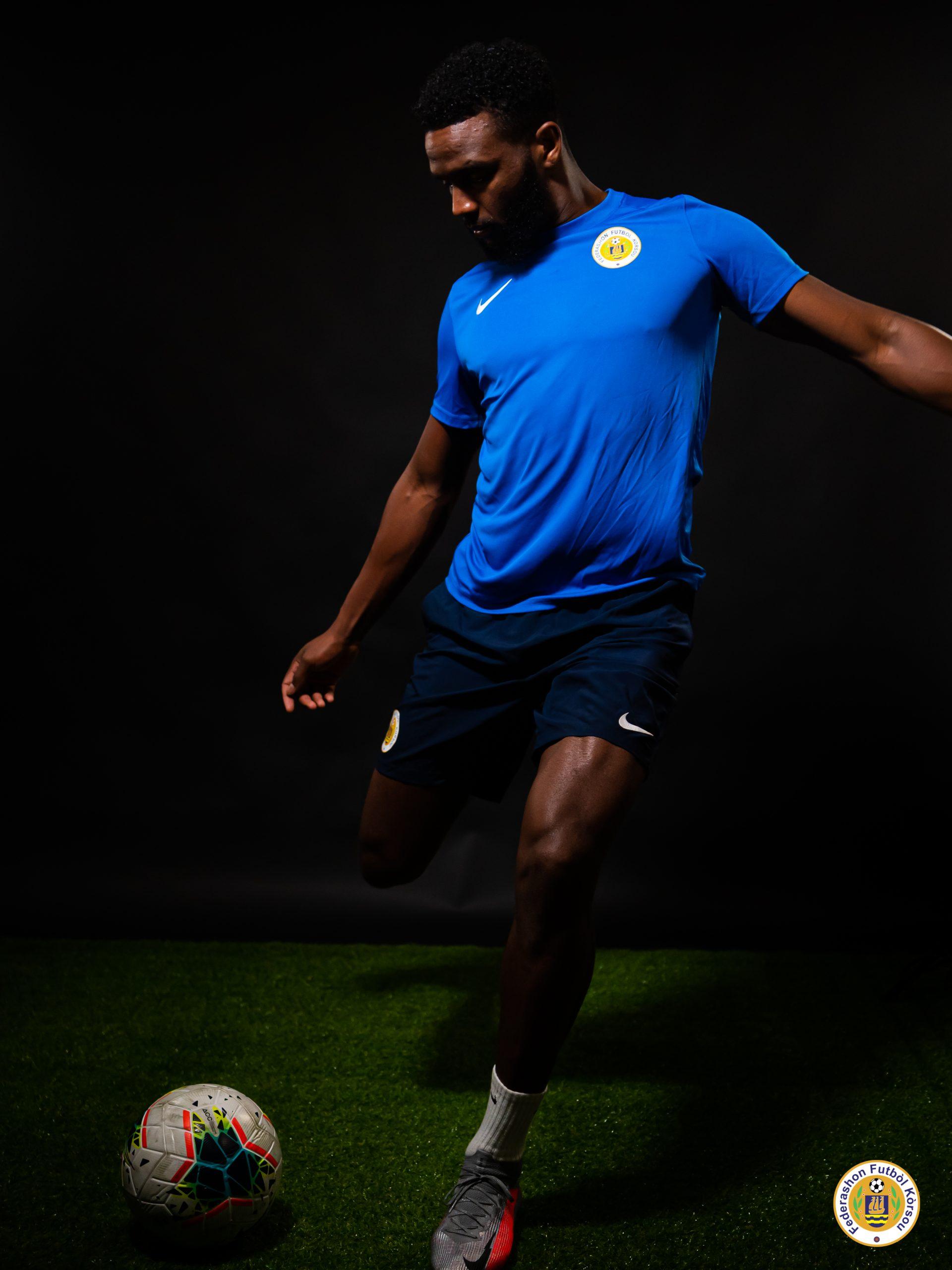 A full body shot from Cuco Martina, kicking a football.